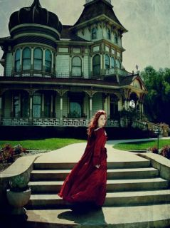 A Girl Standing in Front of a Victorian Mansion Wearing a Flowing Red Dress Photographic Print by Elizabeth May