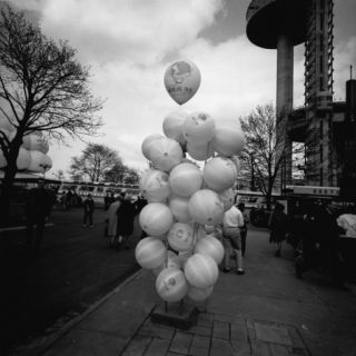 Bunch of Balloons on Stand on Street Photographic Print by George Marks