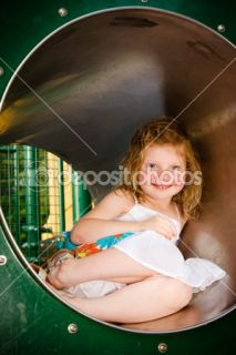 Cute little girl playing in tunnel on playground  Stock Photo